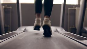 Slow motion footage of supposedly female legs in sneakers running on treadmill. Slow motion footage of supposedly female legs in sneakers running on treadmill stock video footage