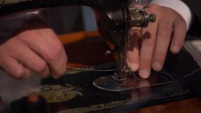 Slow motion footage of a tailor preparing his sewing machine for work
