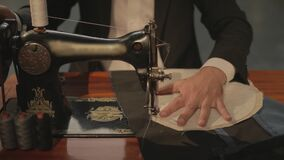 Slow motion footage of a tailor sewing two cloths together on his sewing machine as a practice for the main stitch-flat profile
