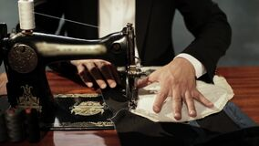 Slow motion footage of a tailor sewing two cloths together on his sewing machine