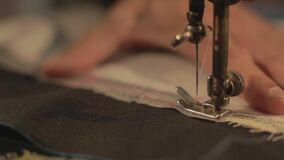 Slow motion footage at the tailors store, the tailor is preparing the final stitch on a cloth