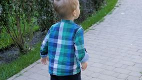 Slow motion video of 2 years old barefoot toddler boy running on fresh green grass at park