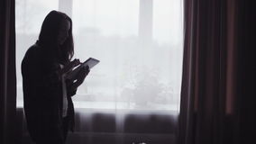 Slow motion footage with a young long haired woman silhouette who is using mobile device indoors. stock footage