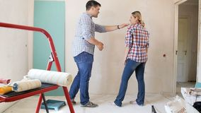 Slow motion footage of young married couple arguing about color of wall at home under renovation. Slow motion video of young married couple arguing about color stock video footage