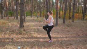 Slow motion footage of young slim woman warming up at forest before running stock video