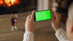 Slow motion video of young woman making photos of burning fireplace on smartphone camera. Green chromakey display for stock footage