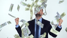 Slow motion of formally dressed man is delighted with the fact that a lot of dollar bills are fall on him