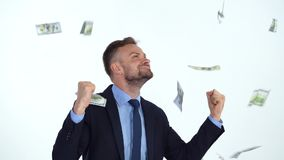 Slow motion of formally dressed man is delighted with the fact that a lot of dollar bills are fall on him stock footage