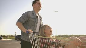 Slow motion: a Free and cheerful man and woman ride in carts in a supermarket Parking lot, shouting and raising their stock video footage