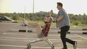 Slow motion: a Free and cheerful man and woman ride in carts in a supermarket Parking lot, shouting and raising their stock video