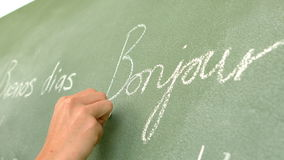 In slow motion french word written on green board stock footage