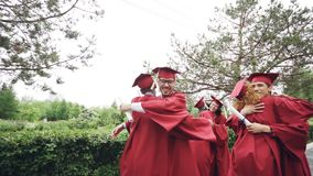Slow motion of friends graduating students doing high five and embracing each other wearing mortarboard caps and gowns. And holding diplomae. Campus, events and stock footage