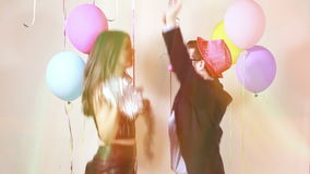Slow motion of funny crazy couple having awesome time dancing. Funny crazy couple having awesome time dancing in party photo booth, graded in slow motion stock video