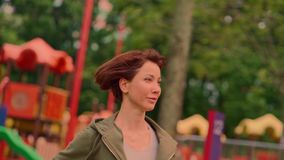 Slow motion gimbal shot tracking in slow motion young attractive and fit woman in hoodie running at green city park. Outdoors slow motion gimbal shot tracking in stock video footage