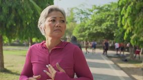 Slomo gimbal tracking attractive middle aged lady running happy at city park . beautiful and sporty 40s woman exercising jogging