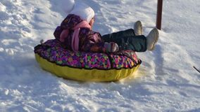 SLOW MOTION:  Girl child rolls on a toboggan running on a sled tubing. The child likes to downhill slope in the winter. Winter sunny frosty day stock footage