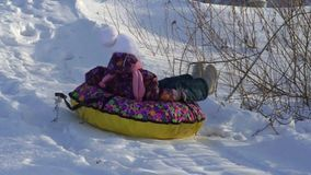 SLOW MOTION:  Girl child rolls on a toboggan running on a sled tubing. The child likes to downhill slope in the winter. Winter sunny frosty day stock video footage