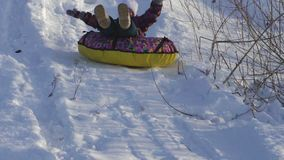 SLOW MOTION:  Girl child rolls on a toboggan running on a sled tubing. The child likes to downhill slope in the winter. Winter sunny frosty day stock video