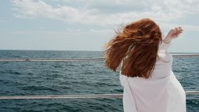 Old fence of the ship between the girl and the sea. The girl enjoys the summer weather on the background of sea waves.