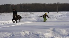Slow Motion: A girl galloping on a horse at a gallop. A horse is dragging a snowboarder guy on a rope. A snowboarder rides on a s. Nowboard in snowdrifts. Girl stock video footage