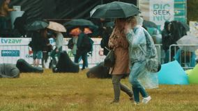 Slow motion girl with mother under umbrella in pouring rain walking at festival stock footage