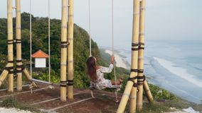 Slow motion, girl swings on swing, enjoys beautiful view of ocean and rests. Traveler woman relaxes on vacation stock video