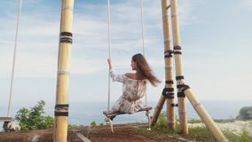 Slow motion, girl swings on swing, enjoys beautiful view of ocean and rests. Traveler woman relaxes on vacation stock footage