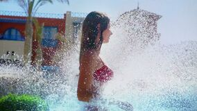 Slow motion of girl under water waterfalls to swim fountain