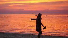 Thailand, Koh Phangan, 3 april. 2016. Girl walking on tropical beach at sunset walking barefoot holding shoes in hands. Slow Motion Girl walking on tropical stock video
