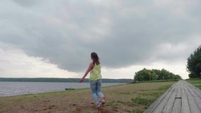 Slow motion of girl in yellow tank and blue jeans leaps for joy on bank of river on cloudy summer day stock footage