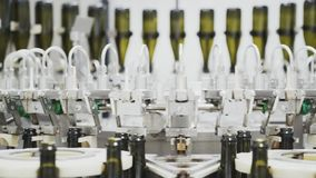 Slow-motion, glass bottles on the automatic conveyor line at the champagne or wine factory. Plant for bottling alcoholic. Beverages stock footage