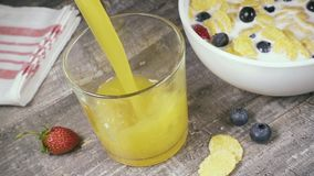 Slow motion in a glass pour a drink next to a bowl of corn flakes top view stock footage