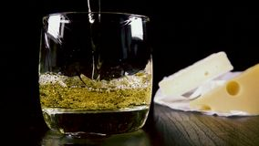 Slow motion strong alcoholic drink pour into a glass near the snack stock video footage