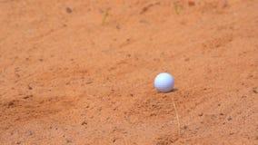 Slow motion golfer hitting swing golf ball on sand bunker stock video