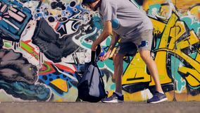 A graffitist collects his paints and walks away. A slow motion of a graffiti artist putting his paints into a backpack and going away stock video