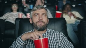 Slow motion of grey-haired man chewing popcorn watching scary movie in cinema