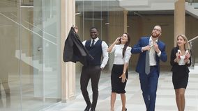 Slow motion. Group confident positive businesspeople exulting of winning. Business people walking along office corridor stock video footage