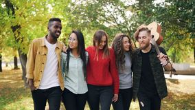 Slow motion of group of young men and women hipsters walking in park together with guitar laughing and talking. Youth stock video footage