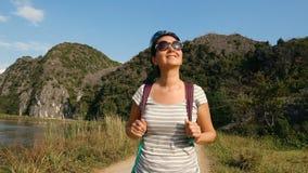 Hiking outdoors on nature. Slow motion handheld camera - hiking outdoors on nature - pretty woman walking through beautiful wetlands in Vietnam. Walking the trek stock footage
