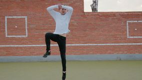 Young handsome guy, a street dancer performing a leap of Grand jete on the Playground. Slow-motion handheld shot of a young cute guy, a street dancer performing stock video
