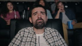 Slow motion of handsome bearded man watching sad movie in cinema stock footage