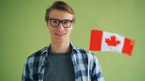 Slow motion of handsome guy in glasses holding national flag of Canada stock video footage