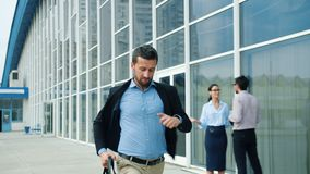 Slow motion of handsome young man running with briefcase along office building