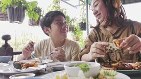 Slow motion of Happy asian family mother and son enjoy eating stock footage