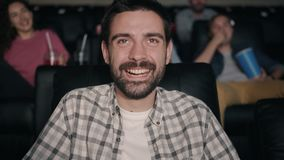 Slow motion of happy bearded man laughing watching film in dark cinema stock video