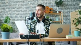 Slow motion of happy blogger recording podcast reading in microphone indoors. In modern home studio sitting at table alone. People and communication concept stock video footage
