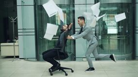 Slow motion of happy business partners having fun in office riding chair and throwing papers contracts enjoying party stock video footage
