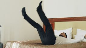 Slow motion of Happy businessman jumping on bed at hotel room and lying relaxed smiling. Business, travel and people stock video footage