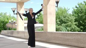 Slow motion - happy businesswoman celebrates something and dances while walking along the city street