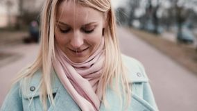 Slow motion happy Caucasian woman texting smiling. Pretty stylish young 20s blonde messaging while walking. Close up. Slow motion happy Caucasian woman texting stock video
